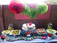 Very Hungry Caterpillar themed birthday party - My daughter Layla's party table, 1 large tiered cake, 1 single cupcake for bday girl, mini cupcakes caterpillar, cake pops in mini flower pots, pigs in a  blanket, goldfish/grapes butterfly ziplock bags, Carmel covered green apple slices, whole apples and pears