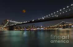 View of the moon rising over the Brooklyn Bridge with a view of the New York City skyline, the Empire State Building and the Manhattan Bridge. The evening lights of the NYC skyline and Bridges are reflected in the water.