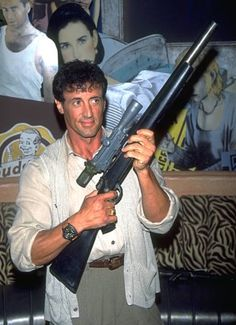 September 18, 1995   Sylvester Stallone holding a large prop rifle or shotgun at Planet Hollywood in Beverly Hills.
