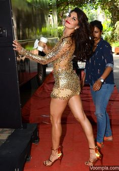Jacqueline shows off hot legs and figure in gold mini dress at Mehboob Studios