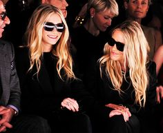 Ashley and Mary-Kate Olsen wear all black with sunglasses at a fashion show