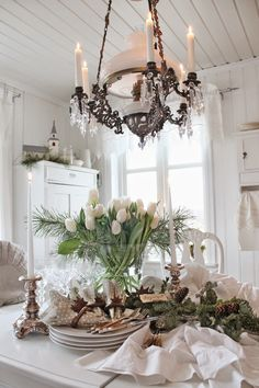 Beautiful Table Scape - Tulips and Pine Boughs. Lovely Light Fixture. Beautiful Room.....New Year's tablescape