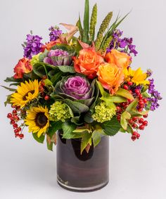 Autumn Delight - This stunning arrangement - filled with beautiful Fall flowers and textures including orange roses, sunflowers, and rose hips - is designed in a glass cylinder lined with a (perfectly seasonal) burgundy ti leaf.