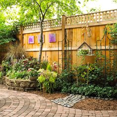 ✤ Landscaping Ideas for Fanciful Fence  Dress up a privacy barrier with accents.  In a mostly hardscape section of the garden, mixing materials heightens visual interest. Here, pavers combine with river rocks and shredded wood for a distinctive edge.  Garden ornaments, including an imaginative birdhouse planter and a series of bright purple paintings, adorn the fence.