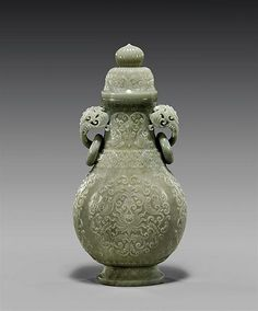 """Estimated Price: $24,000 - $28,000  Description: CARVED CELADON JADE COVERED URN Elaborately carved and finely hollowed, Chinese celadon jade urn and cover; of Mughal-style with openwork foliate handles pending loose rings; the pear shape body with intricately detailed lotus and scrolling foliage; the matching cover surmounted with a fluted peach knop; the jade of light translucent coloration; H: 11 1/4"""""""