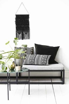 here we see metal and glass mixing perfectly with boho pillows and macrame wall hanging.  literally modern nomad in its most basic form!