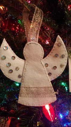 This adorable handmade felt angel features silver thread, silver sequins, and lacy, silver ribbon. Hang it on your Christmas tree, in a window, or use several to create a garland for your mantle. I can change the accents or even the color of the felt upon request. This may