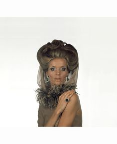 Veruschka with white-silver eye makeup and gold face and body makeup by Olga; a boa of pheasant feathers wraps her neck and a brown organza veil by Valentino; Bulgari jewely; Hair by Alba e Frances…