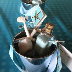 Mermaid party treat buckets:  starfish, shell, sea glass, bottle of bath salts, necklace