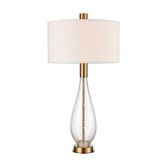Ideal for adding accent lighting to living rooms, hallway consoles, or bedside tables, the tall, elegant body of the Chepstow table Lamp combines retro design aesthetics with updated appeal. This striking design is made from clear, bubble glass and metal fixtures in a luxe, cafe bronze finish. This piece is topped with an oversized, cafe bronze finial that adds the illusion of the neck flowing through the drum-shaped hardback shade in crisp, white linen. - Chepstow Clear Bubble Glass and Cafe Br