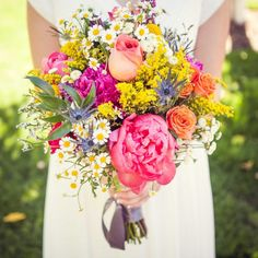 Colorful rustic bouquet. Coral Charm peonies, garden roses, chamomile, billy balls, tulips, golden rod, etc.