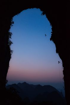 Matt Segal and Cedar Wright rappling from the Great Arch in Ziyun Getu He Chuandong National Park at sunset, China  photo: Carsten Peter