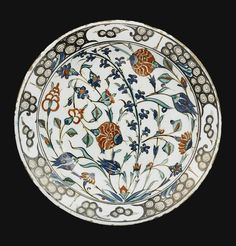 CHROME POTTERY DISH, TURKEY, CIRCA 1570-1580 of deep round form, decorated in underglaze cobalt blue, green and relief red, outlined in black, with a leafy tuft issuing floral sprays, including two large carnations, tulips, hyacinths and prunus branches, the rim with breaking wave pattern, the reverse with alternating circular and floral motifs