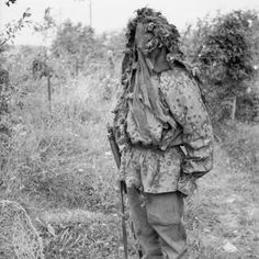 """A sniper demonstrates his camouflage (note: German Waffen-SS Camo Pattern: named unofficially """"Early Plane Tree"""") at a sniper school in a French village, July 27, 1944."""