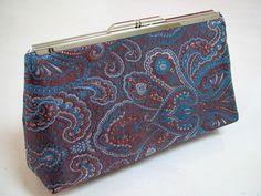 Bolsa em tecido adamascado em tons de azul e marrom. Forrada com cetim branco, acabamentos em costura francesa. Fecho em metal cor prata. R$ 60,00