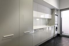Custom made Laundry Renovation. High gloss doors and a subtle dual-tone set-back overhead cupboards.
