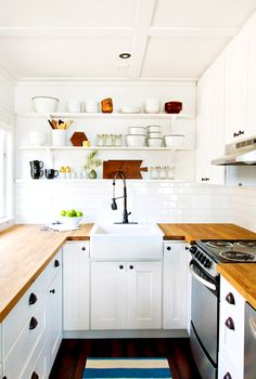 All-white kitchen with white open shelving and wood surface