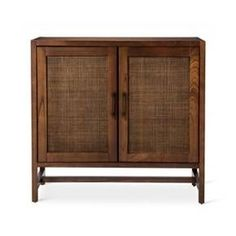 Add some extra storage to any room with this Two-Door Wood & Rattan Accent Cabinet from Threshold™. The small cabinet features two doors with rattan detailing in the center for extra texture and visual appeal. Open the doors to reveal two shelves, one adjustable to properly fit whatever you'd like to store out of sight.