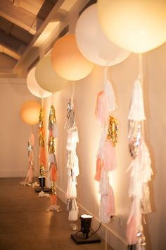 Balloons with tassel garland as string & up lighting. Adds some texture to the room since we won't have a ton of seating.