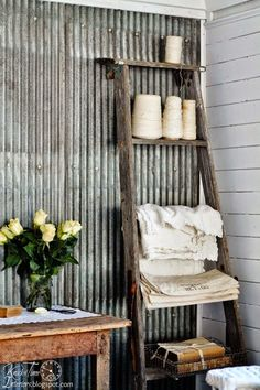 Love the tin wall and the worn ladder for display!
