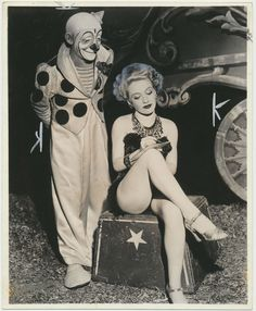 An unidentified Clown poses next to an unidentified Female Circus Performer signing a photograph.  Date on back of photo is May 16, 1946
