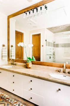 In the master bathroom, touches of wood everywhere create a warm, rustic feel enhanced by the Oriental rug on the floor and the soft brown countertop and tiles in the shower. The large mirror visually helps to open up the room and raise the ceiling.