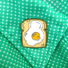 A fried egg on toast. A hearty breakfast, and a most charming accessory.    1 1/4 tall. Black nickle metal finish with raised edges. Butterfly clasp on the back. Possesses magical breakfast powers, which it endows on anyone who wears it. Use with caution.   Want to acquire a bunch of my flair? Use the coupon code PINPOWER at checkout if you buy three or more enamel pins and Ill give you a little discount! YEH.