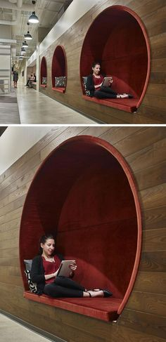 In this modern office, three circular seating nooks with red upholstered cushions are embedded within a dark wood wall, creating a cozy and intimate environment to work or take time away from a screen.