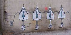 robot graffiti plugged into the wall it's painted on