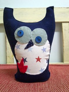 Close-up of felt owl - navy. It is partly filled with plastic pellets and synthetic stuffing. Could work as a book stopper or door stop.