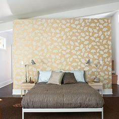 A room divider covered in a gingko-patterned wall paper does double duty as a headboard. The master closet hides behind the wall.