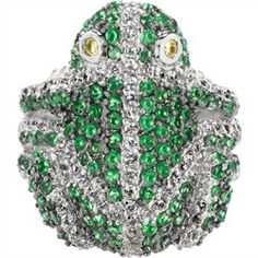 "Zayda's Frog Cocktail Ring has style that's leaps and bounds above all others! This adorable amphibian is perched atop a sterling silver shank, poised and ready to jump to the next lily pad. The frog is coated in pave set, emerald green CZs, giving him that ""just out of the water"" sheen. White stripes of pave set clear CZs extend across his back, hind legs, and head for extra glitter. The shank splits into three at either side of the frog, for extra stability. Each of these three ""branches""…"