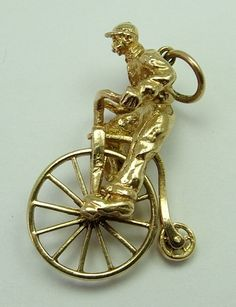 A very large 1960s English 9ct gold charm of a man riding a penny farthing bicycle, with rotating wheels, very nicely detailed with the man sporting a rather fetching moustache, hallmarked for 1966.
