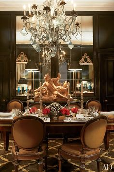 In designers Paolo Moschino and Philip Vergeylen's London flat, the dining room paneling is lacquered black; the Italian dining chairs are antique, the table's centerpiece is by Buccellati, and the terra-cotta sculpture is 18th-century French | archdigest.com