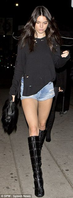 Casual cool: She also sported a long-sleeved black top, knee-high leather booties and a fur bag