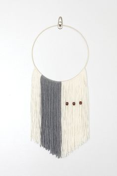 A beautiful neutral yarn wall hanging designed for the modern minimalist. Handwoven, decorated with three walnut colored wood beads and cut in a V