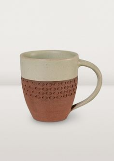 Natural earth tones balance a subdued green glaze in this attractively textured mug. Hard, non-porous and waterproof. Use it every day.