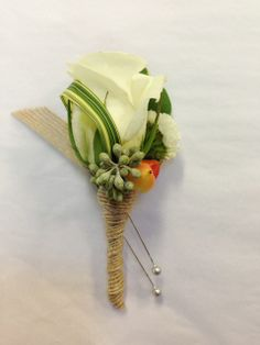 A small white rose boutonniere with a bit of seeded eucalyptus, hypericum berry and variegated lily grass with a rustic burlap ribbon stem wrap...perfect for any rustic, natural wedding. Boutonniere by Seasonal Celebrations. http://www.seasonalcelebrations.com