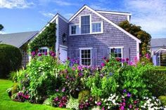 "One of the larger Underhill Settlement cottages, which features a spectacular cutting garden that blooms from early spring through the fall. To a large extent, the character of Nantucket is reflective of these little early homes, author Leslie Linsley writes. They were originally built by and for island residents at a time when some people ""didn't require, didn't desire, or couldn't afford anything larger."""