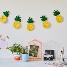 Five yellow felt hanging pineapples with black and white cord. Ideal as a quirky touch to a nursery, bedroom, playroom or even kitchen. Handmade and hanging from a monochrome bakers twine. These can be hung from a shelf or door, above a cot or crib to add a tropical touch. Made to order and entirely customisable. By the secret craft house in Hertford UK