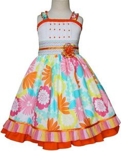 Whimsy summer girls floral dress, beautifully adorned with a smocked band in the waist line and a matching removable bow, transparent orange jewel like buttons are attached to the pleats across the wh