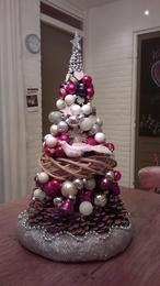 Kerst-toren.  De basis is een kegel van karton, daaroverheen schuif je de kransen en de kerstballetjes en denneappels, of andere leuke accesoires lijm je met een lijmpistool vast.