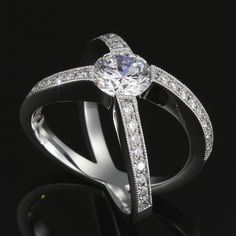 Micro pave' diamond shoulders cradle a 1.00 carat brillant cut diamond.  Cutting edge design that's so surprisingly comfortable - you won't want to take it off! Can be created without shoulder Diamonds.