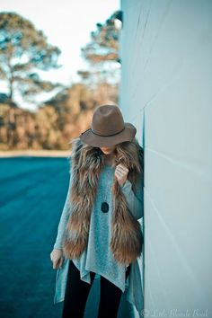 how to wear a fur vest  |  The perfect simple fall outfit consists of a huge sweater, a fur vest, and a floppy hat.
