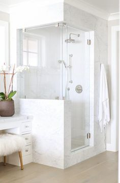 Beautiful beachside bathroom features a corner statuarietto marble frame filled with white glass tiles as well as two shower heads.