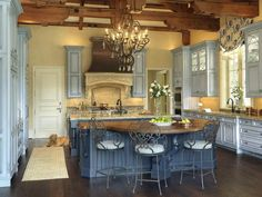 French Country Classic Originating with the classic French palette of blue and butter cream, this grand yet comfortable space is the outcome of immaculate and impressive attention to the finest detail in design and product selection. Ten-foot cabinets visually lower the expansive ceiling with dramatic truss-style beams. A chandelier, an antiqued copper and carved-stone hood and two massive islands are balanced by a warm walnut island top, wood flooring, creamy hues and aged and glazed…