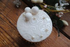 Pearl white lustre powder on white fondant gives a subtle shimmery effect when using with Cake Crafting's Heart Flourish stencil. Topped with small and large edible pearls.