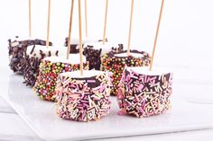 Marshmallows dipping in hot chocolate sauce and in a bowl with sprinkles. Feast!