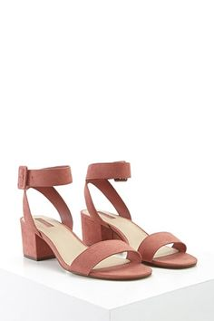 A pair of faux suede sandals featuring buckled ankle straps, a peep toe, and a block heel.
