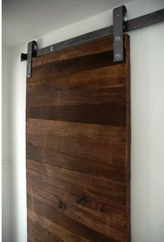 Minimal, contemporary track door made from reclaimed wood—maybe we adapt something like this for wall art? Have wood boards that slide and we can attach current work to them?
